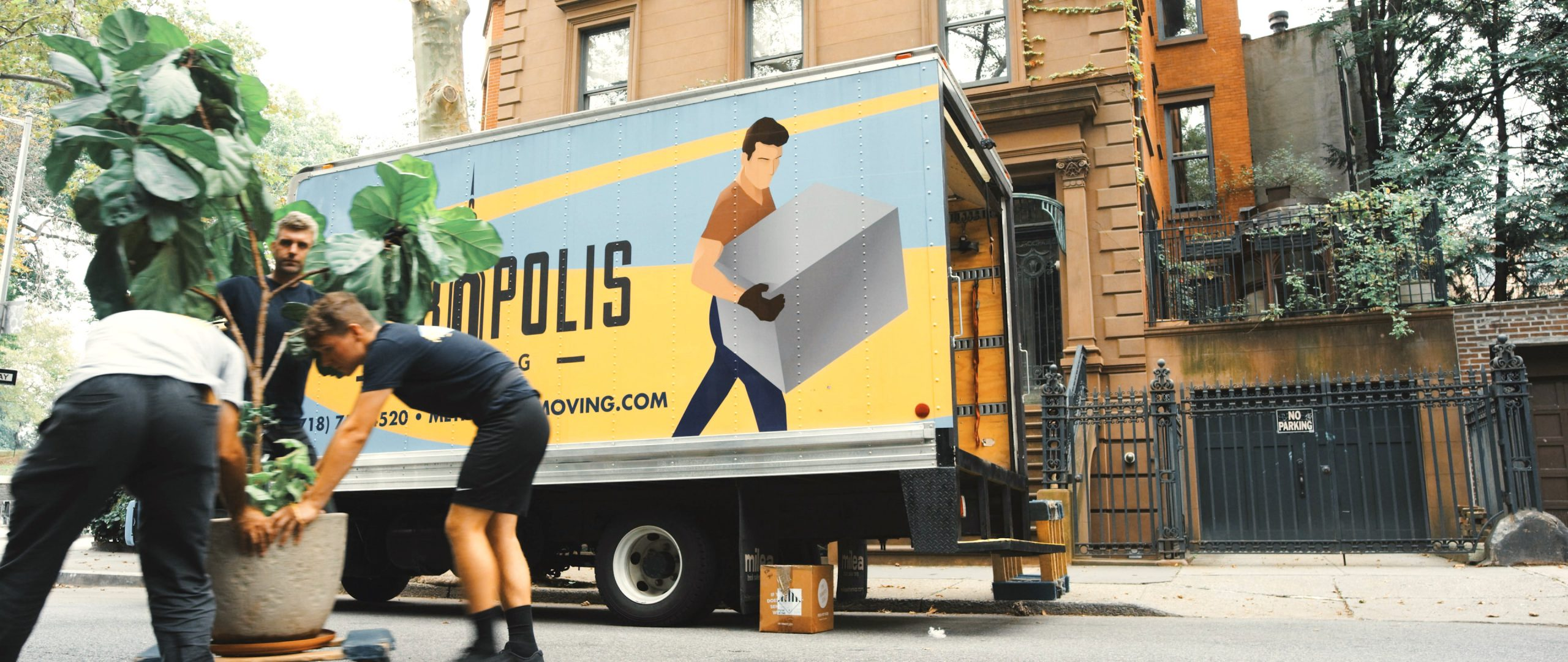 Movers load boxes and a potted plant into a moving van.